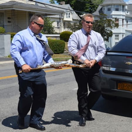 Yonkers Police Detectives Stephen Sokolik and Stephen Kerner carry the crucifix as they return it to the church.