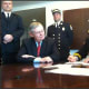 Turn of River Volunteer Fire Department Chief Frank Jacobellis signs an agreement Wednesday consolidating services with the Stamford Fire Department as Mayor David Martin, sitting, looks on.