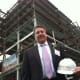 "Christopher Riendeau, senior vice president of fund development, stands in front of the new Stamford Hospital. The hospital celebrated a major milestone in its construction by having a ""topping off"" event. The new hospital will be ready by mid-2016."