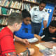 West Point Military Cadet Derrick Hall helps from left Cloonan Middle School students John Liberatore, Daria Domond and Uriel Tofino during a robotics event Tuesday to help spark students interest in science, math and engineering.
