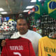 Maynor Gonzalez, owner of Soccer Land, holds up the jerseys of Portugal's superstar Ronaldo and Brazilian favorite Neymar. The World Cup begins Thursday, and Gonzalez believes host Brazil and Germany are the favorites to win.