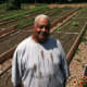 """Fairgate Farm Manager Bill Callion with vegetables growing behind him at Fairgate Farm. Located at 129-143 Stillwater Ave., it is having a free public event called """"It Isn't Easy Being Green,"""" Saturday from noon until 2 p.m."""