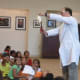 Delighted children look on as Jonah Cohen, the Science Genie from the Children's Museum, performs an experiment above their heads at the Ferguson Library on Thursday.