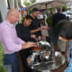 Benny Dedushi, at left, general manager at Solé hands samples during the Taste of the Town Stroll Thursday in New Canaan.