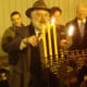 Rabbi Yehoshua Hecht of Beth Israel of Westport and Norwalk continues lighting the menorah.