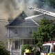 Firefighters attempt to extinguish an Elmsford fire that destroyed one home and jumped to the next on Woodside Avenue in June.