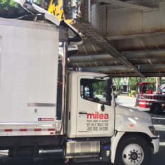 The box truck hit the clearance sign on the train bridge on Friday in South Norwalk.