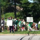 Fairfield residents hold a protest Saturday as they seek to have sound barriers built at the I-95 northbound rest area. Construction materials can be seen behind them at the Exit 22 rest stop.