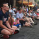 Audience members grab a chair, or a bit of sidewalk, to listen to the Boston Pops perform on Bedford Street on Monday.