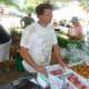 Jonathan Kirchner, the farmer at Wilton's Ambler Farm, speaks with a customer at the Wilton Farmers Market.