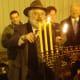 Rabbi Yehoshua Hecht of Beth Israel of Westport and Norwalk continues lighting the menorah.
