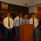 Horace Greeley High School football captain Teddy Graves (at podium) was joined by teammates in support of coach Bill Tribou at a Board of Education meeting May 1.