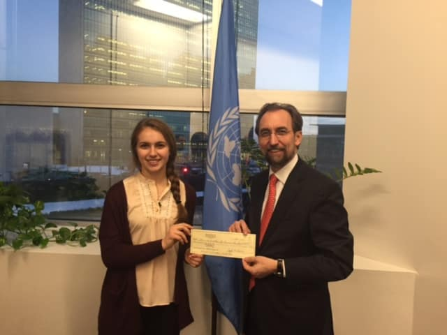 Champion fencer Sylvie Binder presenting a check to the United Nations Human Rights Office. Photo Credit: Sam Barron