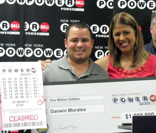 Somers resident Darwin Morales received an oversized check Tuesday in Fishkill from New York Lottery's Yolanda Vega for $1 million.