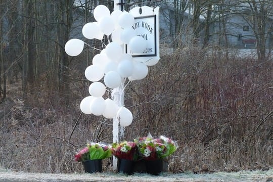 Balloons and flowers hang from the Sandy Hook School sign in Newtown only six months ago when 26 students and teachers were killed at the school.