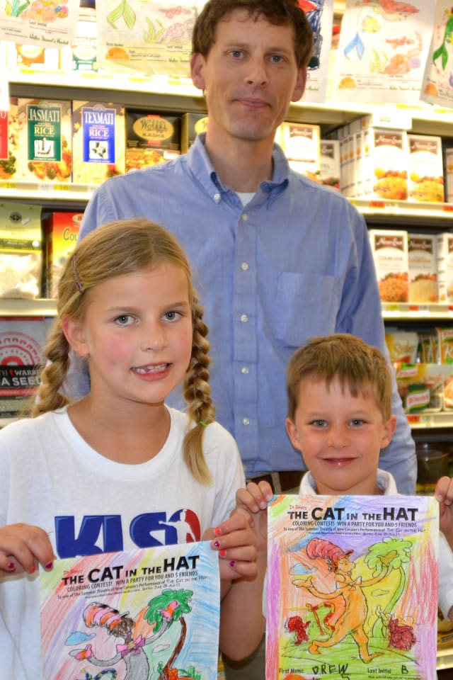 Alex Stewart, general manager of Walter Stewart's, back, stands with coloring contest winner Drew Burr, right, and Miller Burr, a coloring contest finalist.