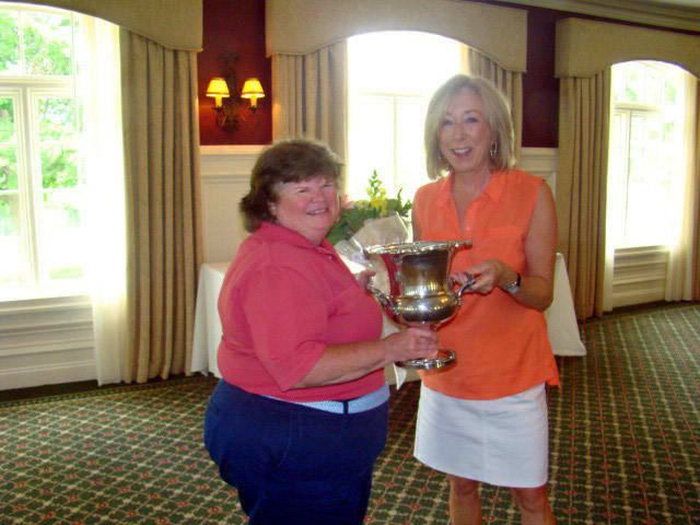 Laurie White holds the North Salem Women's Championship Golf Trophy with Cathy Cossari, board member of the Salem Golf Club.