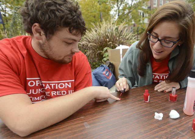 """Participants in a 2012 """"Operation Jungle Red"""" event at WCSU take the pledge against domestic violence and have their pinky nail painted red to affirm the commitment to non-violence."""