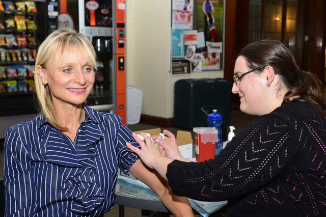 Marcia O'Kane, executive director of the Greenwich Chamber of Commerce, receives a flu shot from Greenwich Hospital nurse Christina DeVito.