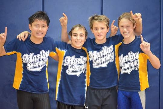 Greenwich YMCA Marlins swimmers, from left, Conway Zhou, Stefan Todorovic, Christian Farricker and Marcus Hodgson celebrate their record-breaking race at a recent meet.