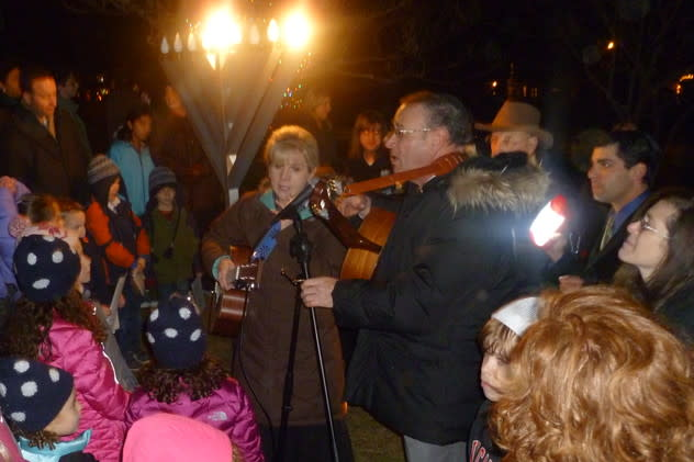 Cantor Shirah Sklar, left and Rabbi Mark Lipson of Temple Shalom in Norwalk lead the singing of songs Tuesday night at the lighting of the Menorah at God's Acre in New Canaan.