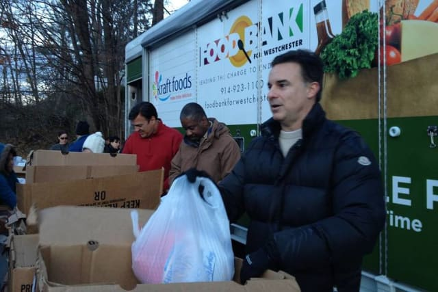 Food Bank for Westchester board members Charles Day, Willard Hill Jr., and Scott Boilen hand out food during a turkey distribution event for the Mount Kisco Interfaith Food Pantry.