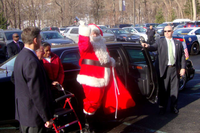 Santa Claus, protected by U.S. Secret Service agents, steps out of a presidential limo at Arc of Westchester in Hawthorne.