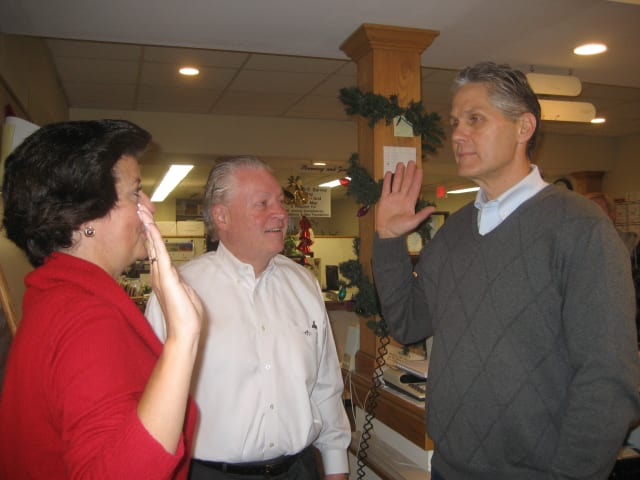 Fairfield Town Clerk Betsy Browne swears in Thomas Conley while First Selectman Mike Tetreau looks on.