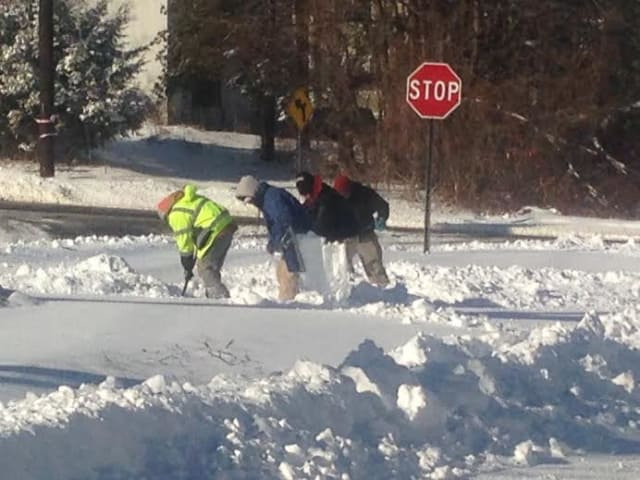 A crew of workers bundles up from head to toe to clear the snow from a Ridgefield sidewalk.
