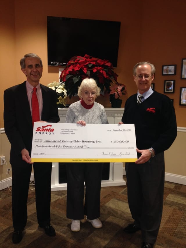 Carolyn Durgy, President of the Board of Directors of Sullivan McKinney Elder Housing, accepts the check from Santa Energy Corporation.