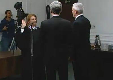 Mayor Thomas Roach joins John Martin as he is sworn in as Common Council president by Judge Jo Ann Friia.