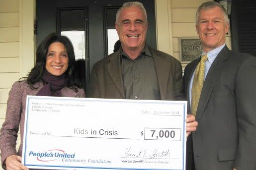Alon Marom, Director of Development, Corporate and Community Giving for Kids in Crisis (center) accepts the chck from Karen Galbo and Michael Keady.