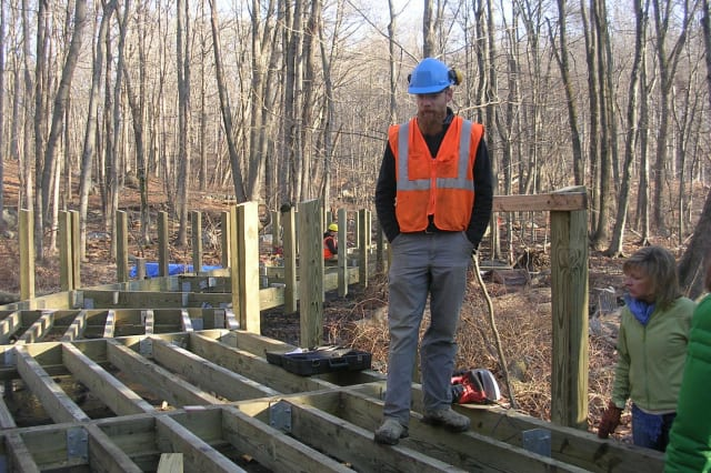 Josh Ryan monitors construction of a boardwalk as part of the Norwalk River Valley Trail.