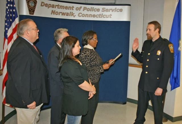 Sgt Markert is administered the oath of office by Commissioner Collier-Clemmons, in the presence of his wife, while Mayor Rilling and Commissioner Yost look on.