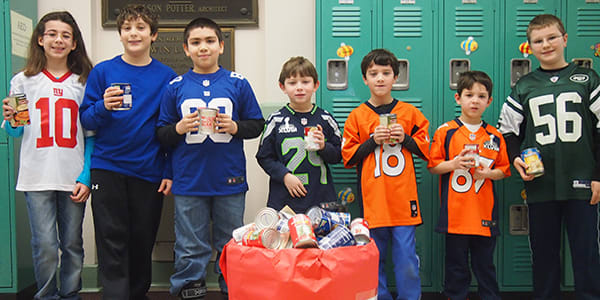 "Parsons Elementary School students are shown with cans collected in ""Souper Bowl."""