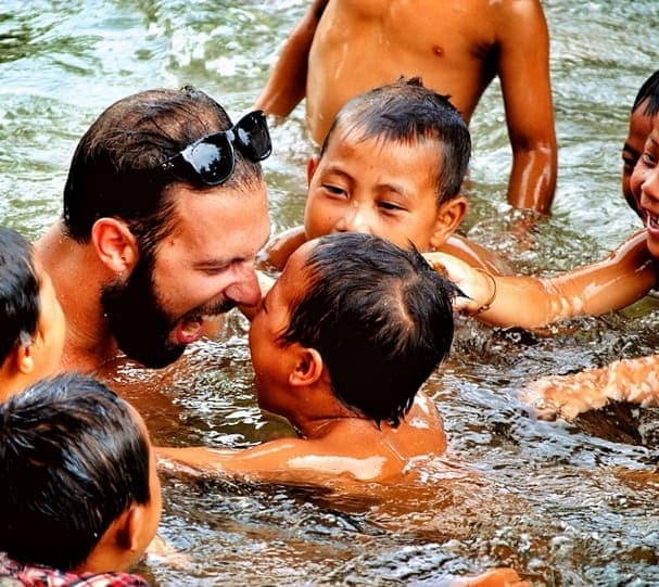 Harry Devert playing with local children on a previous trip to Laos.