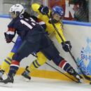 Julie Chu of the United States slams Michelle Lowenhielm of Sweden into the boards during the third period of Monday's game.