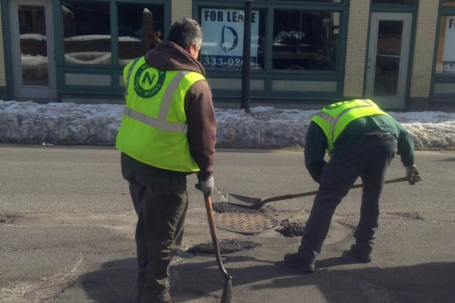 A Department of Public Works crew in Norwalk repairs potholes on Water Street.