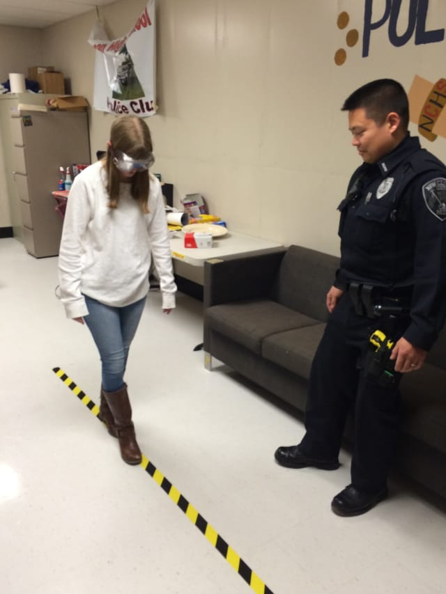 Eliza Haney navigates a straight line while wearing Fatal Vision Goggles that simulate the impact of alcohol on coordination.