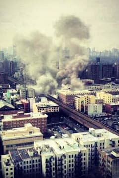 Fire crews are battling a blaze following a huge explosion that collapsed a building in Harlem and has suspended all Metro-North traffic in the city.