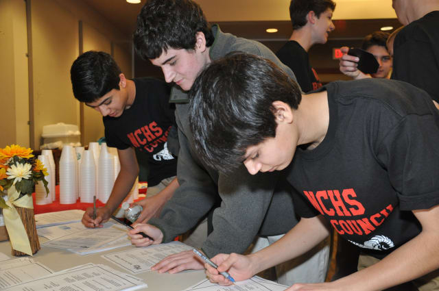 New Canaan High students sign a pledge to not text and drive.