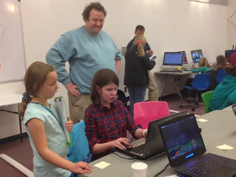 Minecraft Tournament judge Victoria observes winner Chloe Ammerman-Gerke's creation along with father Chris.