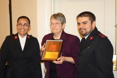 HPCW Executive Director Mary Spengler; (center) receives a plaque from Salvation Army representatives Lorena Castillo, left, and Alexis Castillo.