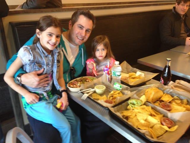 Josh Salles, of Larchmont, eats lunch with his daughters and wife (not pictured).