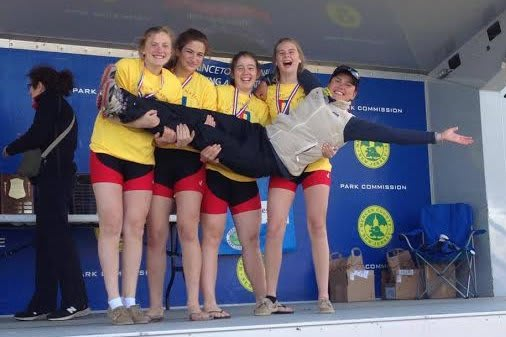 Maggie Owen, Tate Aronstein, Siobhan Naughton and Kim Dyrvik with coach Anna Cherednikova, celebrate a gold medal in the Novice 4x.