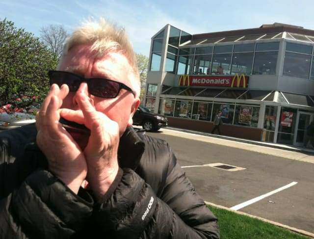 Stamford musician Steve Morrell plays a short tune on his harmonica outside the East Main Street McDonald's restaurant in Stamford. He welcomes the updating of Ronald McDonald's wardrobe for the chain's clown mascot.