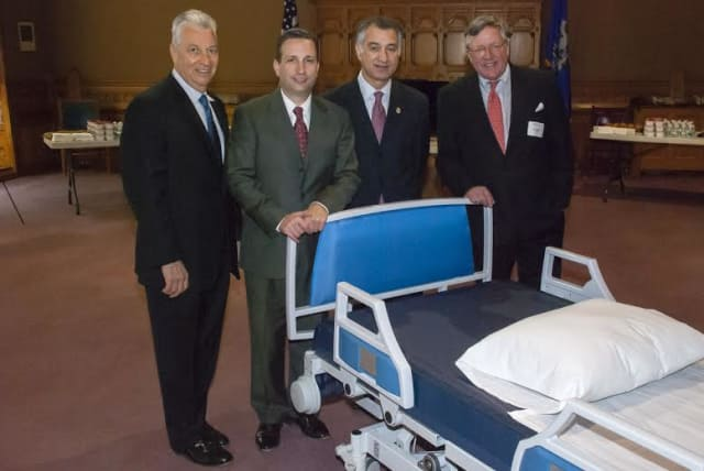 Sen. Carlo Leone and Sen. Bob Duff pose with executives of Norwalk-based Next Health Inc., whose new integrated hospital bed and wheelchair/commode system is helping patients stay in their homes.