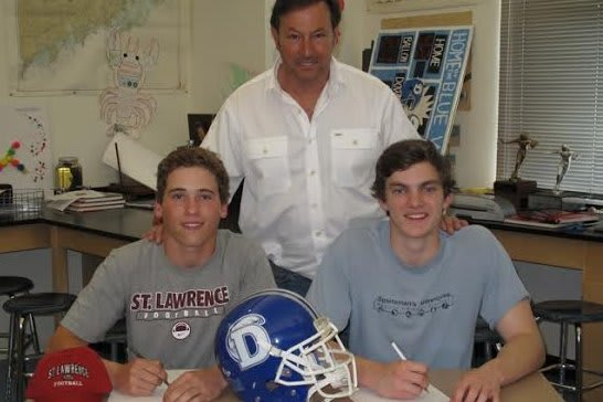 Darien football players Daly Hebert, left, and Silas Wyper, right, announced their college plans with coach Rob Trifone.