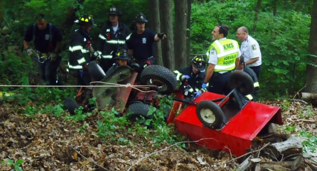 Norwalk firefighters help a man injured in a lawn tractor accident Tuesday evening.