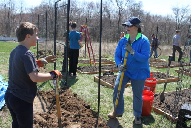 Adult volunteer Doni Wisdom (right) stops to chat with Boy Scout Christopher Lanni as they work at Grace's Hill Farm, a new community garden at Our Saviour's Lutheran Church in Fairfield.